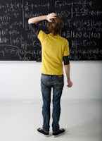 student in front of filled chalk board
